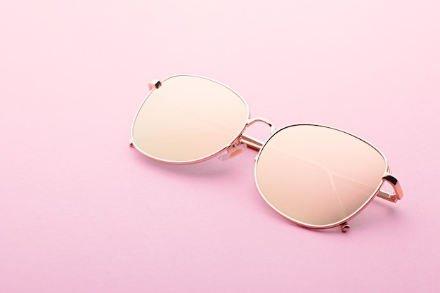 Classic aviator mirrored flat lens sunglasses with golden metal frame closeup on pink background, top view