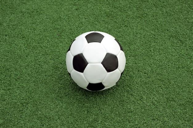 검은 색 액센트가있는 흰색 축구를위한 클래식 공은 스포츠 운동장 중앙 근처의 마킹 라인에 녹색 합성 잔디 위에 놓여 있습니다.