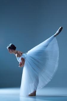 Classic ballerina dancing on blue