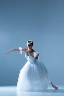 Classic ballerina dancing on blue