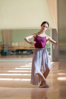 Classic ballet dancer posing at barre on rehearsal room