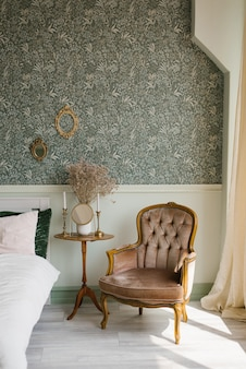 Classic bedroom interior. a brown armchair by the window and the bed and the bedside table with a mirror and candles on it