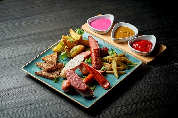 Классическая закуска к пиву - ассорти из жареных мясных колбас, картофеля, маринованных огурцов в тарелке с соусами. продовольственный паб