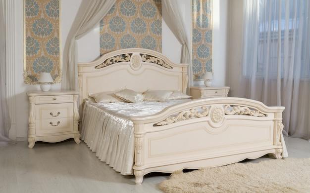 Классическая бежевая кровать и ящики в спальне