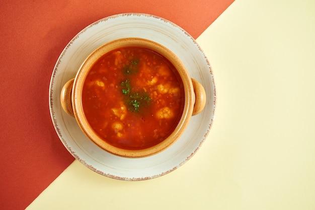 Классический бельгийский красный суп с помидорами и небольшими фрикадельками в глиняной тарелке на цветной поверхности.