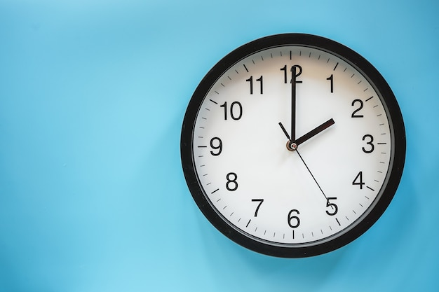 Classic black and white analog clock on blue background at two o'clock with copy space
