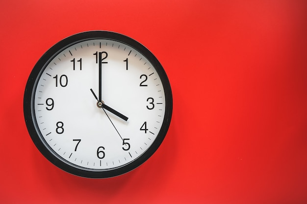 Classic black and white analog clock on red background at four o'clock with copy space