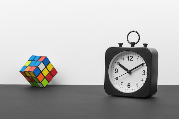 Classic black and white clock and a multicolored cube on a black and white background. crassic dial.