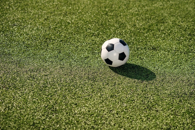 A classic black and white soccer ball lies on soccer field