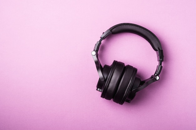 Classic black wireless headphones on pink minimal background