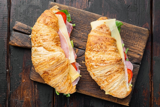 Classic blt croissant sandwiches set, on old dark  wooden table background, top view flat lay