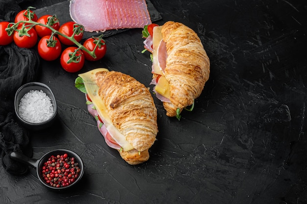 Classic blt croissant sandwiches set, with herbs and ingredients, on black stone background, with copy space for text