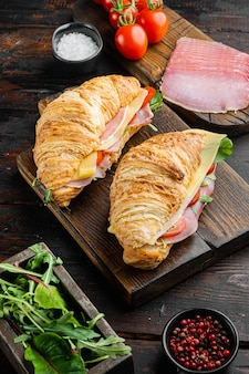 Classic blt croissant sandwiches set, with herbs and ingredients, on old dark  wooden table background