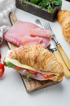 Classic blt croissant sandwiches set, with herbs and ingredients, on white stone  background