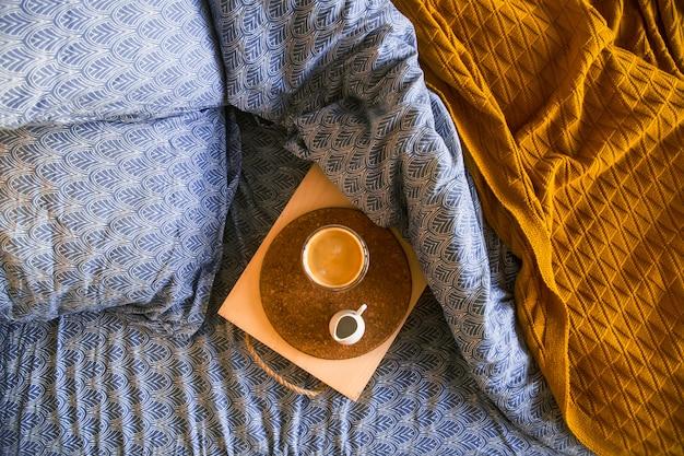 コーヒーとミルクジャグのトレイを備えたクラシックなブルーの寝具。