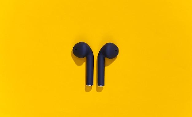 明るい黄色の背景にクラシックブルーカラーの真のワイヤレスbluetoothヘッドフォンまたはイヤフォン。