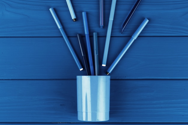 Classic blue colored top view photo of scattered stationery