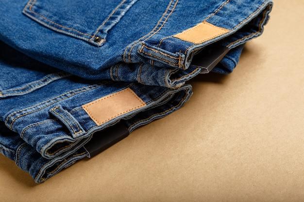 クラシックなブルージーンズ。コピースペースとベージュの工芸品の背景に茶色の空白の革のラベルとカジュアルパンツ服ブルージーンズ。