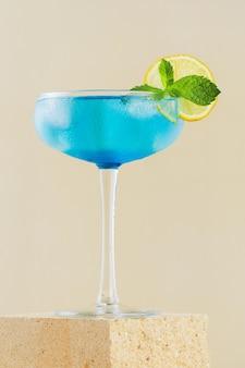 연단에 현대적인 정물에 레몬을 넣은 클래식 블루 라군 칵테일