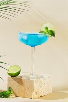 Классический коктейль голубая лагуна с лимоном на современный натюрморт на подиуме