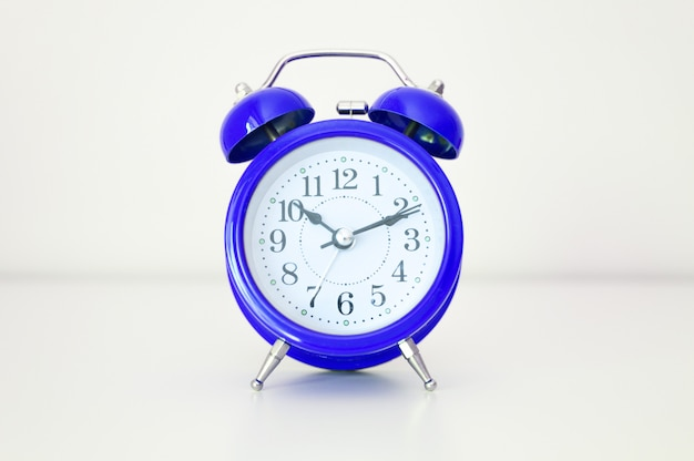 Classic blue round analog alarm clock on white background.