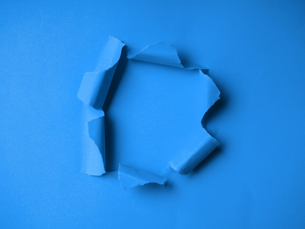 Classic blue tinted, classic colors in 2020, hole in the paper with torn side. torn paper on classic blue color
