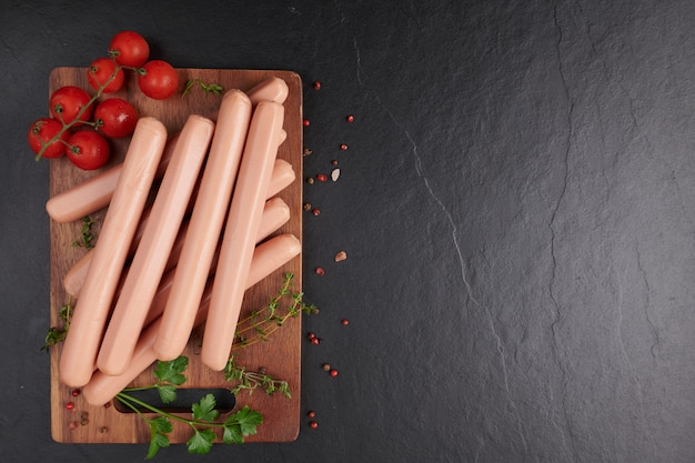 Classic boiled meat pork sausages on chopping board with pepper and basil, parsley, thyme and cherry tomatoes. snack for kid. black background. sausages with spices and herbs, selective focus.