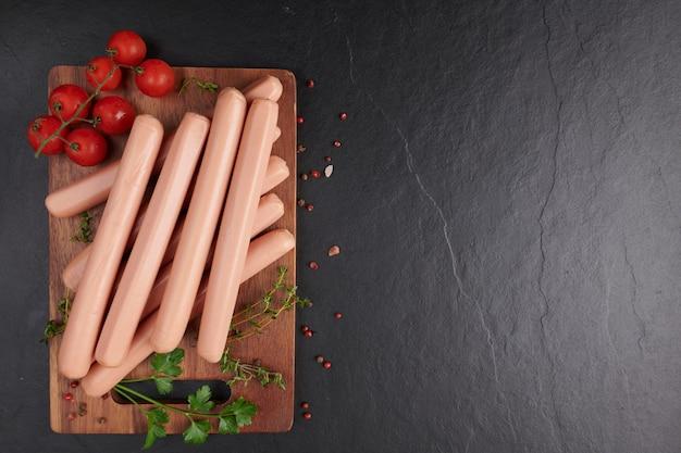 Классические сосиски из отварного мяса из свинины на разделочной доске с перцем и базиликом, петрушкой, тимьяном и помидорами черри. закуска для малыша. черный фон. колбасы со специями и зеленью, выборочный фокус.