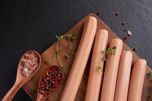 Классические сосиски из отварного мяса из свинины на разделочной доске с перцем и базиликом, петрушкой, тимьяном и помидорами черри. закуска для малыша. черная поверхность. колбасы со специями и зеленью, выборочный фокус.