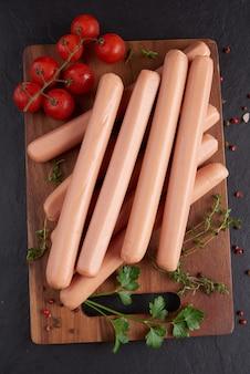 후추와 바질, 파슬리, 백리향, 체리 토마토와 함께 보드를 자르고 클래식 삶은 고기 돼지 고기 소시지.