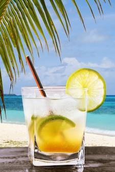 海を背景にしたカイピリーニャの作りたてのアルコール飲料のクラシックなブラジルカクテル