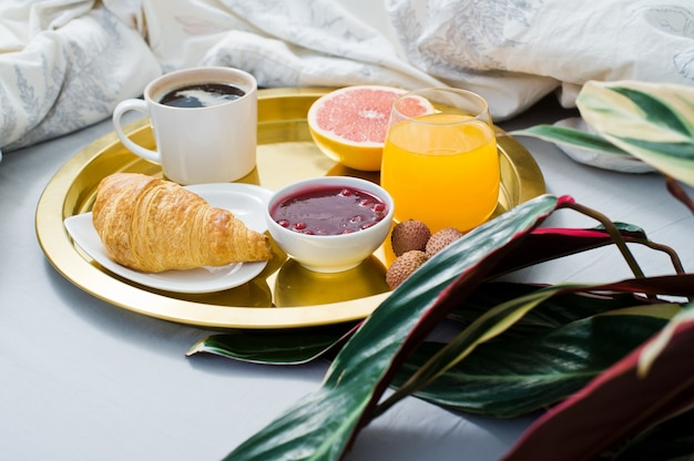 Classic breakfast in bed, hotel service. coffee, jam, croissant, orange juice, grapefruit, lychee.