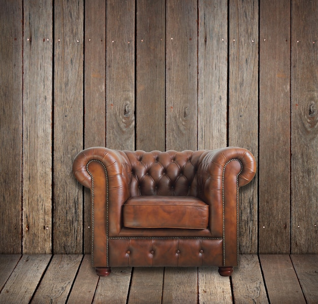 Classic brown leather armchair in wooden room.