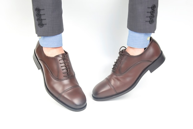 Classic brown men's leather shoes dressed on hands on a white