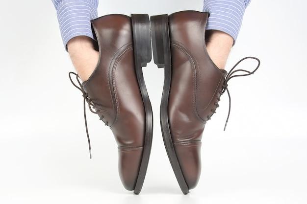 白い背景の手に着用する古典的な茶色の靴