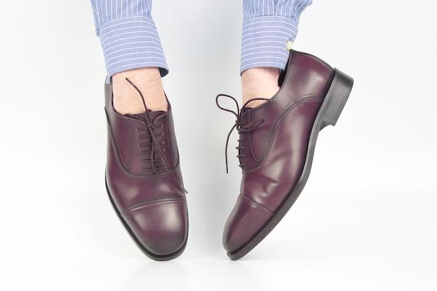 白い背景の上の手に着用する古典的な茶色の靴