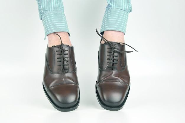 白い表面の手に着用する古典的な茶色の靴