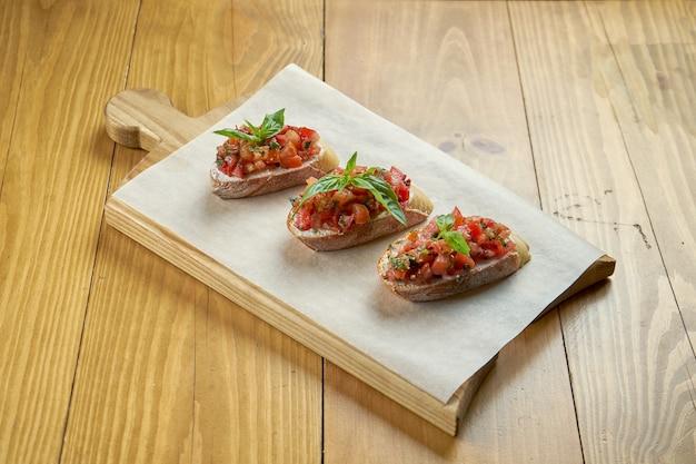 木の板にトマト、オリーブオイル、バジルを添えたクラシックなブルスケッタ。イタリアの前菜