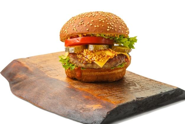 牛肉、白い背景の上の木の板にゴマとパンのソースでチーズ野菜と古典的なハンバーガー。横の写真