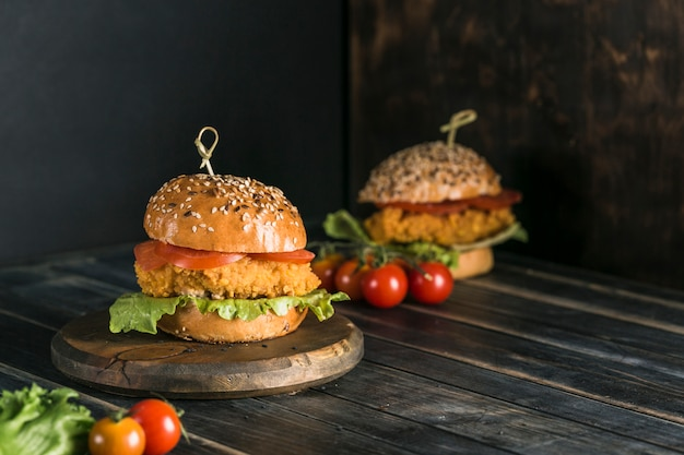 ゴマトマト、レタス、マスタードソースのパンに鶏肉を入れたクラシックなハンバーガー。