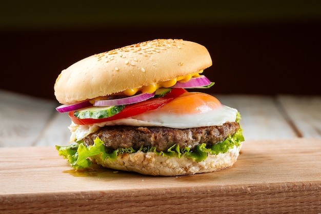 Classic burger with egg on the wooden board
