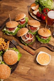 赤いトマトの横にある木製のまな板の上の古典的なハンバーガー。焼きビーフ。グリーンレタス。おいしいチーズ。