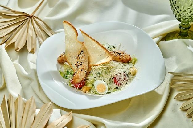 Классический салат цезарь с курицей и гренками, пармезаном и помидорами черри в белой тарелке на скатерти