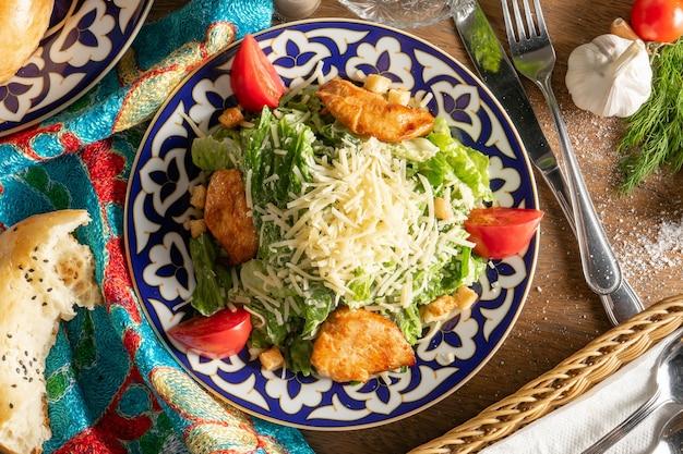 Классический салат «цезарь» с куриным филе, помидорами и пармезаном в тарелке с традиционным узбекским узором.
