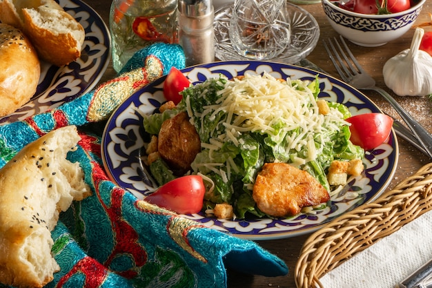 Classic caesar salad with chicken fillet, tomatoes and parmesan cheese in a plate with a traditional uzbek pattern.