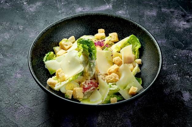 セラミックボウルにクルトン、パルメザンチーズ、ホワイトソースが入ったクラシックなシーザーサラダ。クローズアップ