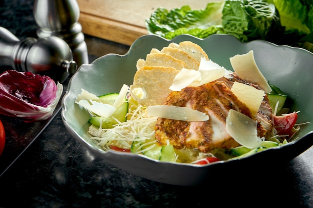Классический салат «цезарь» с гренками, пармезаном, курицей гриль, подается в зеленой миске на темном мраморном столе. ресторанная еда.