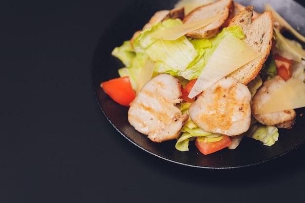 鶏胸肉のグリルと卵の半分を白いセラミックプレートに入れたクラシックなシーザーサラダ。古い紺色の木製の背景の上に上記の材料を添えて。上面図、スペース。