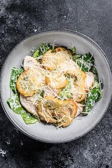 Классический салат «цезарь» с куриной грудкой на гриле, пармезаном и листьями салата ромен.