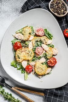 鶏胸肉のグリル、パルメザンチーズ、ウズラの卵、トマト、ロメインレタスのクラシックなシーザーサラダ。白色の背景。上面図。